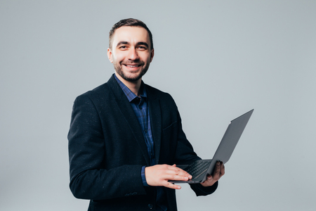 Side view of attractive businessman in classical suit using laptop, standing against gray background Фото со стока