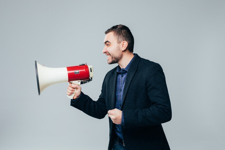 portrait of young man shouting with megaphone against a white background