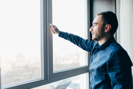 Man is opening the window at home to refresh the room