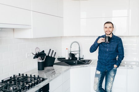 Young man smiling and holding coffee in the kitchen