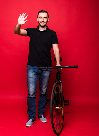 Handsome young man with bicycle on red background