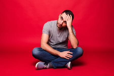 Porträt eines fröhlichen jungen Mannes, der auf einem Boden sitzt, isoliert auf rotem Hintergrund Standard-Bild