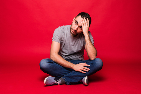Retrato de joven alegre sentado en el suelo aislado sobre fondo rojo. Foto de archivo