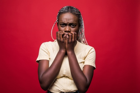 Headshot of beautiful scared young dark-skinned European woman closing mouth not to scream, feeling frightened and terrified, her eyes and look full of fear and terror isolated on red background
