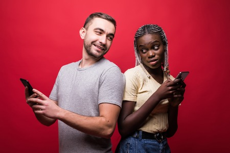 Happy couple sending text messages from phone side by side on red background Stock Photo