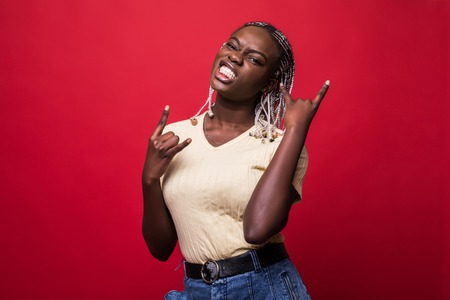 Beautiful young african american woman shouting with crazy expression doing rock symbol with hands up over red isolated background.