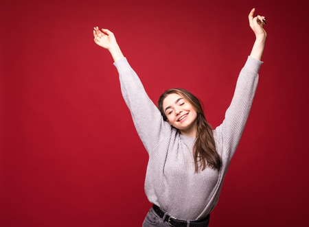 Dancing happy cheerful woman in red in joyful dance. Energetic image of joyous beautiful young woman on red background.