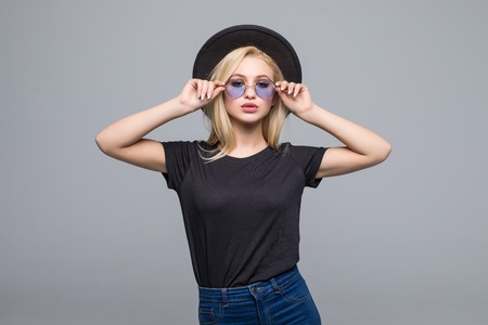 Young sexy blonde woman sending a kiss and posing in the white wall,wearing frock, swag hat,mirrored summer round sunglasses, bright summer make up,show happy emotions,Lifestyle bright toned colors.