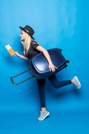 Young woman with suitcase and passport running on blue background.