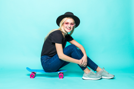 Smiling young woman sitting and posing on skateboard over green background 免版税图像