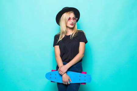 Young girl in black fluffy hat holding a skateboard and looking at the camera isolated on green background