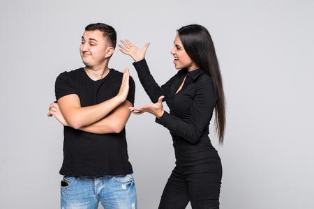 Portrait d'un jeune couple en colère ayant un argument isolé sur fond gris, criant