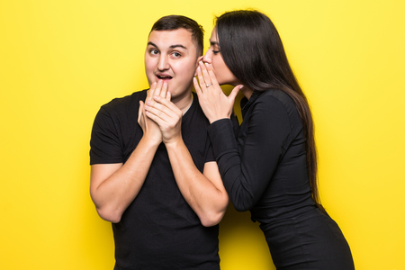 Excited beautiful woman telling secret to her man standing over yellow background,