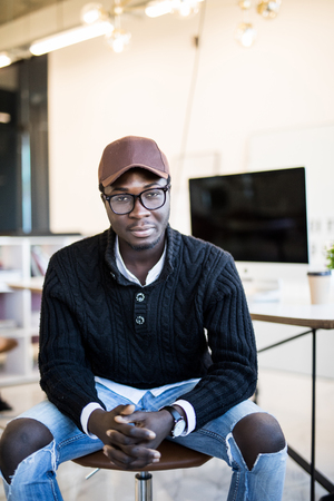 Smiling African man sitting on chair at his modern office. Concept of happy business people. Stock fotó - 122616899