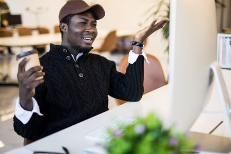 Shocked african businessman in suit feeling stunned by online news looking at computer screen sitting at workplace with laptop, stressed trader investor surprised by stock market changes Stock Photo