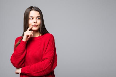 Jolie jeune femme portant des vêtements décontractés pensant, avec le doigt sur les lèvres, regardant la caméra et debout isolé sur fond blanc.