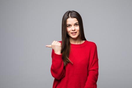Geschokt aantrekkelijke vriendin in trendy rode trui, terugwijzend op grijze achtergrond