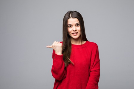 Shocked attractive girlfriend in trendy red sweater, pointing back on gray background