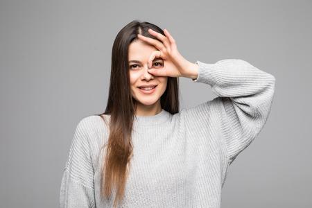Close up retrato de hermosa mujer alegre sonriendo, mostrando dientes blancos, mirando a la cámara a través de los dedos en gesto bien.