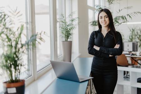 Retrato de mujer de negocios exitosa de pie en su oficina.