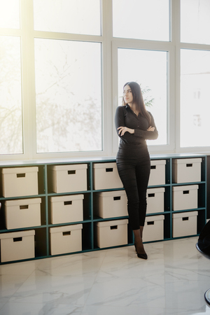 Smiling business woman standing with folded arms in office. Woman in formal business attire standing in front of her desk in office.
