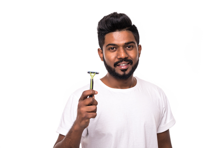 Handsome young man standing with razor in hand on white background. Men care concept.