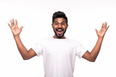 Felice giovane indiano che gesticola e sorride mentre sta in piedi su uno sfondo bianco