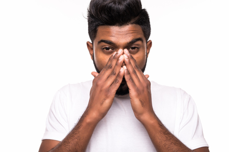 Portrait of sick young indian man with allergy or germs cold, blowing his nose with tissue, looking miserable unwell very sick, isolated on white background.
