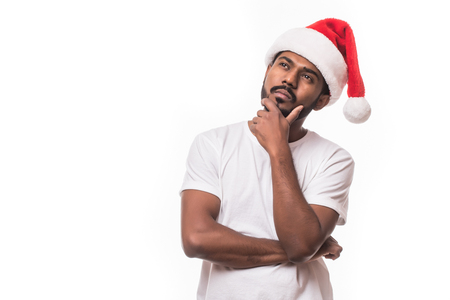 Indian pretty man in santa hat thinking isolated on white background