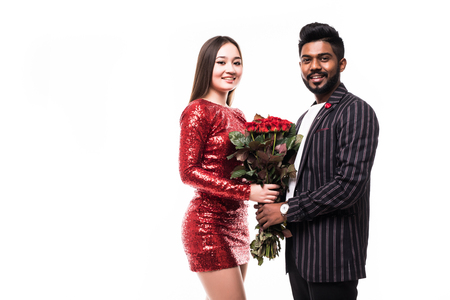 Beautiful romantic couple in love isolated on grey background. Attractive young woman holding red roses while hugging her handsome man. Banque d'images