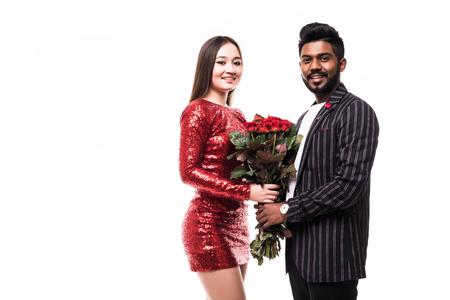 Schönes romantisches Paar in der Liebe lokalisiert auf grauem Hintergrund. Attraktive junge Frau, die rote Rosen beim Umarmen ihres gutaussehenden Mannes hält.