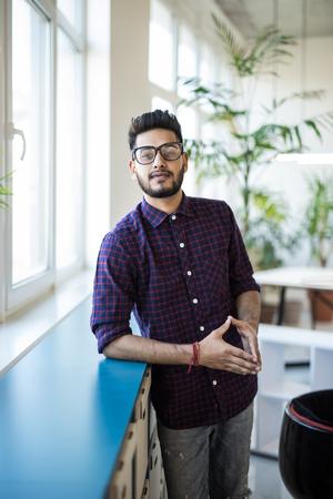 Retrato de hombre de negocios feliz en ropa casual de pie en la oficina moderna cerca de las ventanas