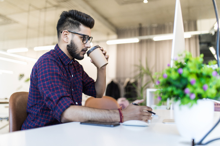 Young indian man drinking coffee while working in office