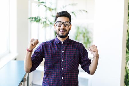 Hombre celebrando su éxito, fondo de oficina moderna.