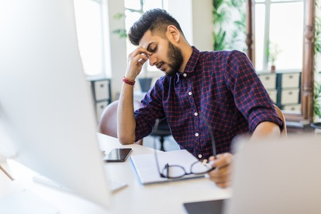 Photo of an Indian male frustrated with work sitting in front of a laptop. Stock Photo