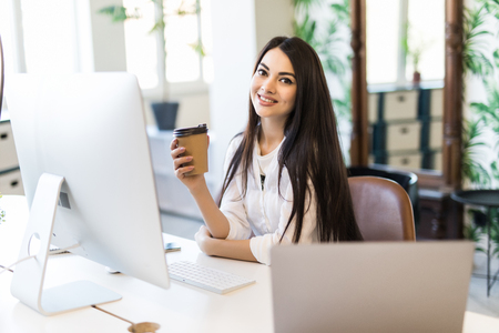 Happy businesswoman holding cup while typing on laptop in her office