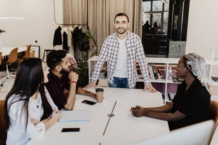 Businessman interacting with coworkers during meeting in office Banco de Imagens