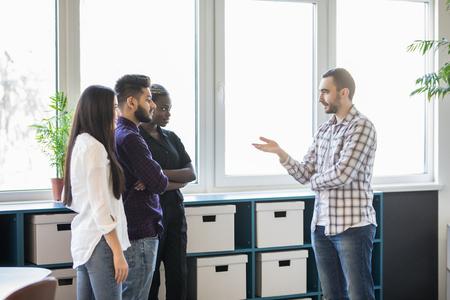 Informal meeting of team standing at break in modern office