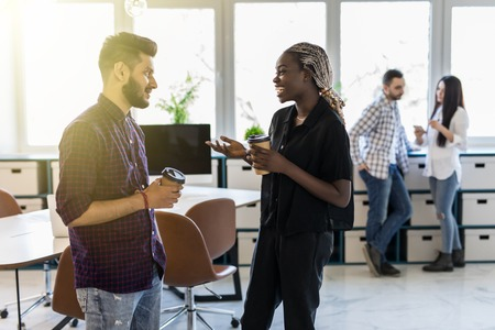 Diverse friends two coworkers standing at office distracted from work drink coffee having informal talk. Boss employee planning new project discuss interesting idea companionship concept Stock Photo
