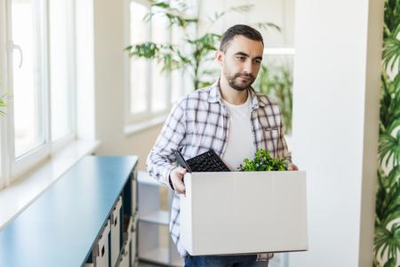 Geschäfts-, Entlassungs- und Arbeitsplatzverlustkonzept - entlassener männlicher Büroangestellter mit einer Kiste mit seinen persönlichen Sachen und seinen traurigen Kollegen