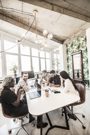 Group of young modern people in smart casual wear discussing business while sitting in the creative office Stock Photo