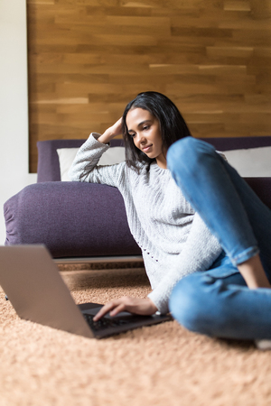 Young woman sitting on wooden floor with coffee in interior and using laptop Stock Photo