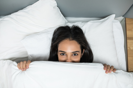 Beautiful young woman lying down in the bed and sleeping. Teen girl with open eyes covers her face with white blanket in the morning. Do not get enough sleep concept. View from above. Banco de Imagens - 124450575