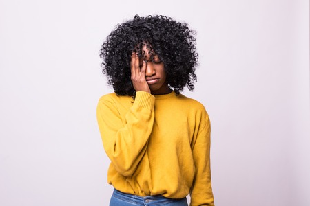 Sad pretty girl feeling upset while spending time at home alone. Beautiful young dark-skinned female with Afro hairstyle staring at camera against studio wall