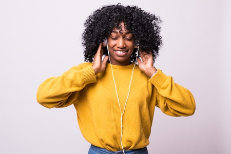 Adorable african woman in yellow sweater singing and having fun while listening to music using wireless earphones over white background 写真素材