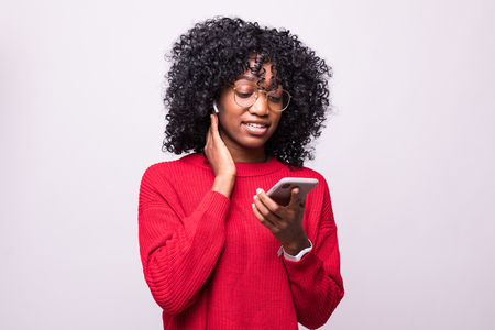 Portrait of african woman talking earbuds or listening to music on her mobile phone isolated white background