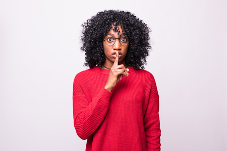 Portrait of beautiful young dark-skinned woman asking to keep silence holding finger on her lips