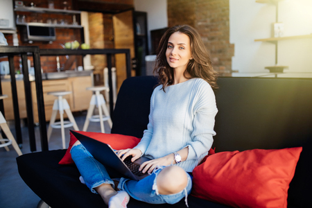 Cheerful woman sitting on her couch using laptop at home in the sitting room