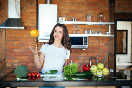 Young woman having fun in kitchen, juggle with vegetables Banque d'images