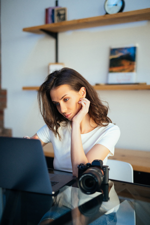 Freelance photographer woman with camera at home editing photos on computer
